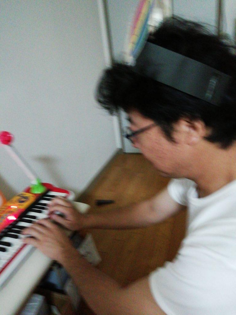 おもちゃのピアノを弾くおじさん